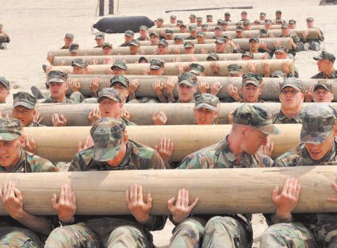 Soldiers aspiring to become Navy SEALS trying to overcome a physical ordeal: keep a log sum of 225 kilograms. Teamwork is a constant in their lives. / defense.gov